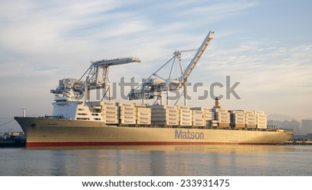 OAKLAND, CA - NOVEMBER 27, 2014: Matson Cargo Ship MAHIMAHI at the Port of Oakland at sunrise on Thanksgiving morning. Loading cranes are silent as workers enjoy the holiday home with their families. - stock photo