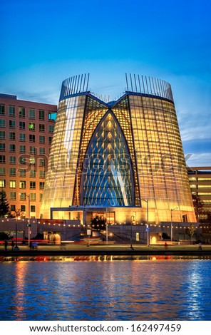 OAKLAND, CALIFORNIA - NOV 10, 2013: Dramatic contemporary glass cathedral illuminated at night on Lake Merritt in downtown Oakland. The award-winning architectural landmark was built in 2008. - stock photo