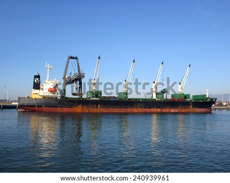 OAKLAND - JANUARY 3:  Shipping boat is unloaded by cranes in Oakland Harbor on a clear day. Fourth busiest container port in country, it's a major economic engine in the California.  January 3, 2012. - stock photo