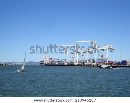 OAKLAND - MAY 23:  Cargo Cranes, tugboat, sail boat in Oakland Harbor on a nice day with San Francisco bridge and city in distance. Fourth busiest container port in the country of USA.  May 23 2010. - stock photo