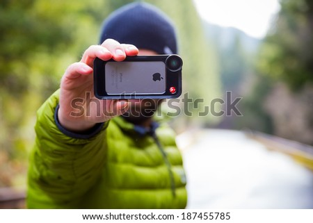 OAKRIDGE, OR - FEBRUARY 19, 2014: Photographer using an iPhone 5S with Manfrotto lens attached outdoors. - stock photo