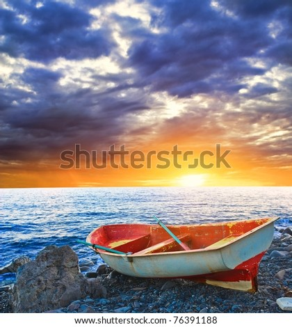 oar boat on a sea coast by a sunrise - stock photo