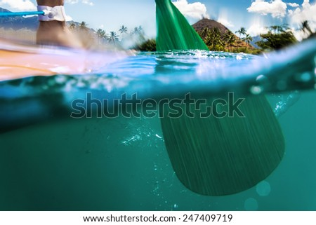 Oar of paddle boarder half way submerged in ocean water paddling - stock photo
