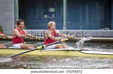 Oarsmen during the explosive first strokes of a rowing race - stock photo