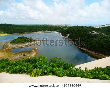 Oasis in dunes with vegetation and cloudy sky in Natal, Brazil - stock photo