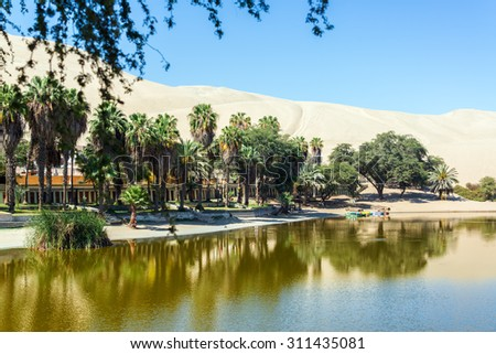 Oasis of Huacachina, Peru with sand dunes in the background - stock photo