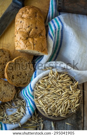 Oat and bread on the wooden background with blue linen napkin. Selective focus. View from above. - stock photo