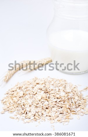 Oat and wheat flakes with milk on white background.