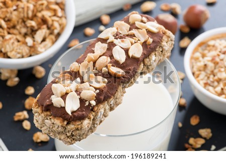 oat bar with chocolate and nuts, a glass of milk, close-up, horizontal - stock photo