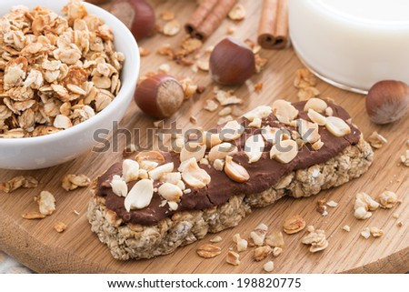 oat bar with chocolate on wooden board, horizontal - stock photo