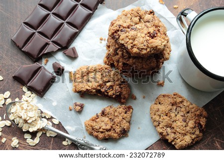 Oat cookies with chocolate and mug of milk - stock photo