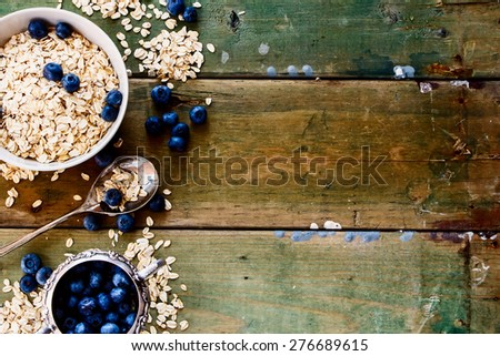 Oat flake and fresh berries in bowl on rustic wood. Background with space for text. Top view. - stock photo