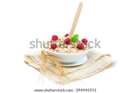 Oat flakes and fresh fruits raspberries in a bowl with a wooden spoon and ears on canvas isolated on white background. - stock photo