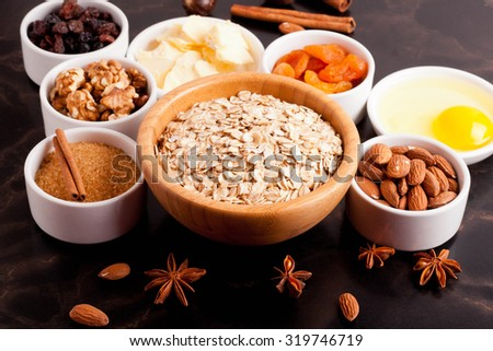 oat flakes and ingredients on a black table, top view, close-up, horizontal