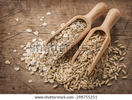 Oat flakes and seeds  in spoons - stock photo