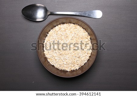 Oat flakes and spoon on table. Healthy food concept. - stock photo