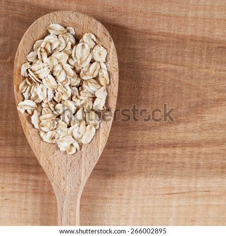 Oat flakes in a spoon on a wooden board. - stock photo