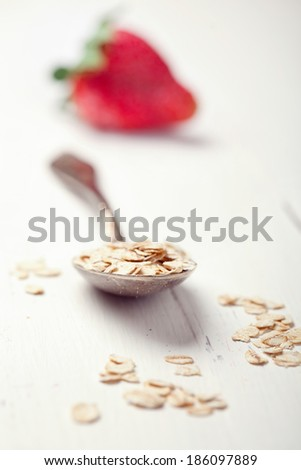 Oat flakes in an old spoon and a strawberry on wooden table, selective focus, toned photo