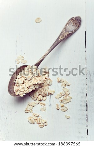 Oat flakes in an old spoon on wooden table, toned photo, simple diagonal composition - stock photo