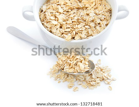 Oat flakes in bowl and spoon on white background - stock photo