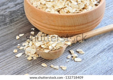 Oat flakes in bowl and wooden spoon on old wooden background - stock photo