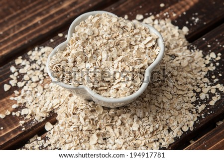 Oat flakes in bowl on wooden table.