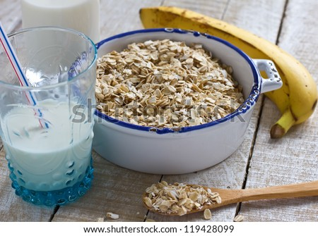 Oat flakes in  bowl with banana and milk on wooden table. Selective focus. - stock photo