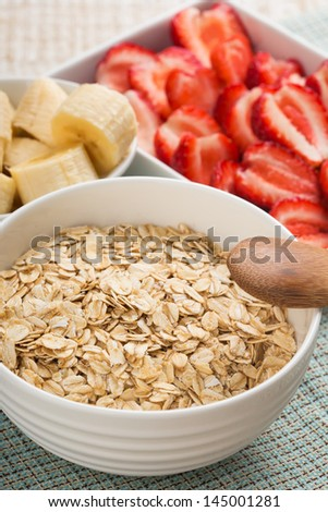 Oat flakes in bowl with banana and strawberry on wooden table. Selective focus.