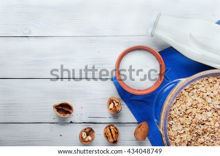 Oat flakes in glass pan bottle of milk, plate with shugar, walnut on blue cloth .White wooden background.Top view.free space