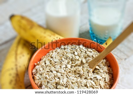 Oat flakes in orange bowl with banana and milk on wooden table. Selective focus. - stock photo
