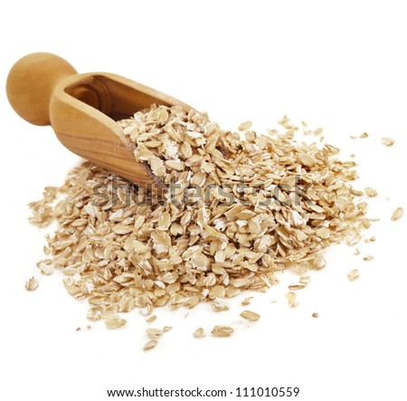 Oat flakes in wooden scoop isolated on white background - stock photo