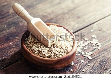 Oat flakes in wooden scoop on wooden background - stock photo