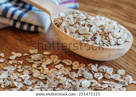 oat flakes in wooden spoon on wooden background - stock photo