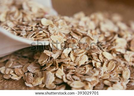 Oat flakes. Oatmeal. Organic oatmeal. Oat flakes on a wooden bac - stock photo
