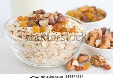 Oat flakes, raisins, walnuts, milk on a white background. - stock photo