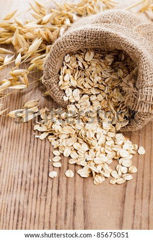 Oat flakes spilling from the burlap bag on wooden table - stock photo