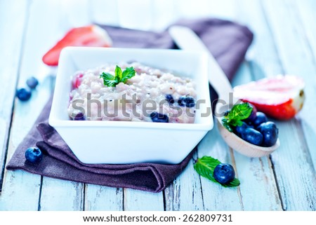 oat flakes with fruit in bowl on a table - stock photo