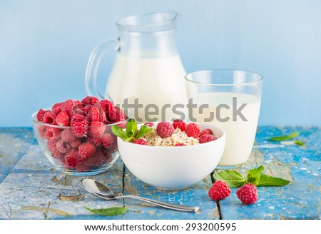 Oat flakes with milk and fresh raspberries for breakfast, glass and jag with milk, spoon, fresh mint on an old wooden blue background. The concept of a healthy diet, weight loss - stock photo