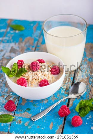 Oat flakes with milk and raspberries for breakfast, glass with milk, spoon,  fresh mint on an old wooden blue background, the concept of a healthy diet, weight loss - stock photo