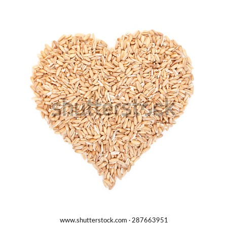 Oat grains laid out in the shape of heart isolated on white. Top view.
