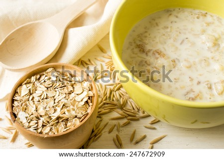 Oat milk porridge in a yellow bowl on the table with oats - stock photo