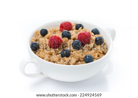 oat porridge with berries in a bowl, isolated on white - stock photo