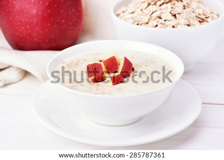 Oat porridge with red apple slices on white wooden table - stock photo