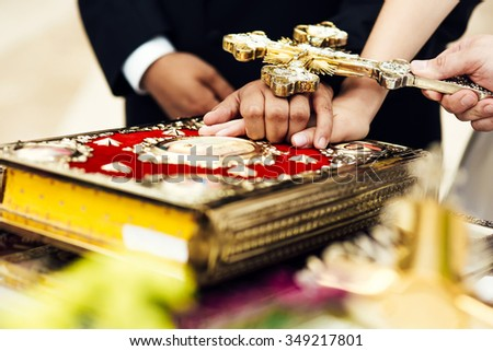 Oath at the newlyweds on luxuriously decorated bible. Hands of men and women in the church near the altar, the priest cross. - stock photo