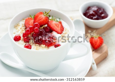 Oatmeal and fruits in white cup with spoon on wooden board for ...