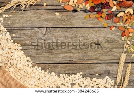 Oatmeal and various delicious ingredients for breakfast - dried fruits and nuts on wooden table. Healthy breakfast concept. Ingredients for homemade granola. Copyspace background. Top view. - stock photo