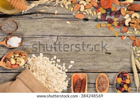 Oatmeal and various delicious ingredients for breakfast - dried fruits, nuts and honey on wooden table. Ingredients for homemade granola. Copyspace background. Top view. - stock photo