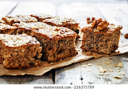 oatmeal cake with dates and walnuts on a dark wood background. tinting. selective focus on walnut - stock photo