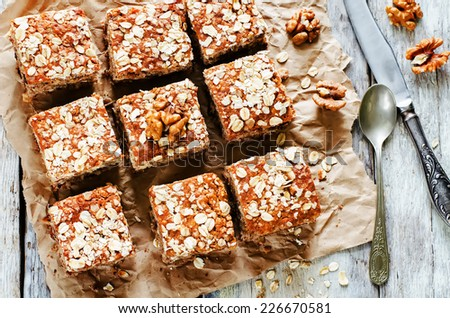 oatmeal cake with dates and walnuts on a light background. tinting. selective focus on walnut - stock photo
