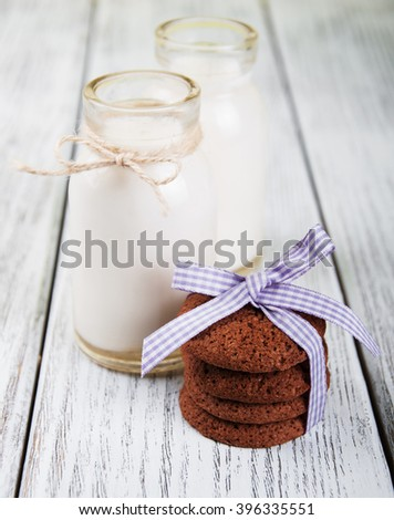 oatmeal cookies and bottles of milk on a old wooden table